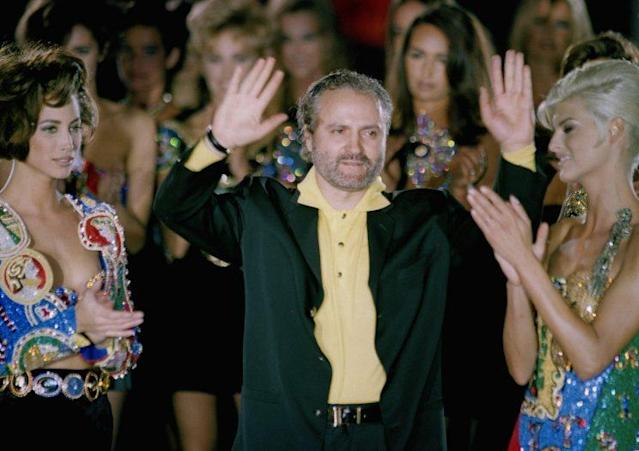 Surrounded by models, Versace waves to the audience at the end of the Milan runway show of his Fall 1991 Ready-to-Wear collection. (Photo: AP Images)