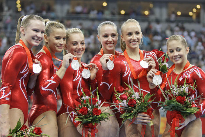 FILE - U.S. gymnasts, from left: Bridget Sloan, Alicia Sacramone, Samantha Peszek, Chellsie Memmel, Nastia Liukin, and Shawn Johnson pose with their silver medals after the women's team final competition at the Beijing 2008 Olympics in Beijing, in this Aug 13, 2008, file photo. Memmel started doing gymnastics again when the COVID-19 pandemic hit last spring because it felt like one of the few things in her life she could control. The 32-year-old former world champion and Olympic silver medalist discovered more than an outlet for stress. She rediscovered her love for the sport, so much so the married mother of two is making an unlikely comeback.(AP Photo/Amy Sancetta, File)