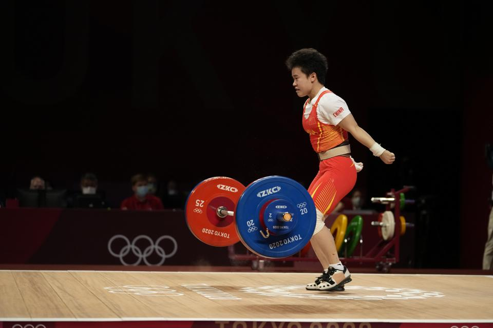 Hou Zhihui of China competes in the women's 49kg weightlifting event, at the 2020 Summer Olympics, Saturday, July 24, 2021, in Tokyo, Japan. She won the gold medal and sets Olympic record. (AP Photo/Luca Bruno)
