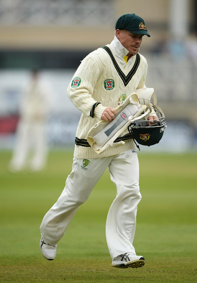 NOTTINGHAM, ENGLAND - JULY 10:  David Warner of Australia runs a helmet and shin guard off the pitch during day one of the 1st Investec Ashes Test match between England and Australia at Trent Bridge Cricket Ground on July 10, 2013 in Nottingham, England.  (Photo by Gareth Copley/Getty Images)