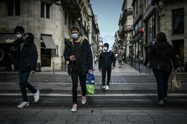 Pedestrians cross a street in the mandatory face mask zone to limit Covid-19 infections in Bordeaux