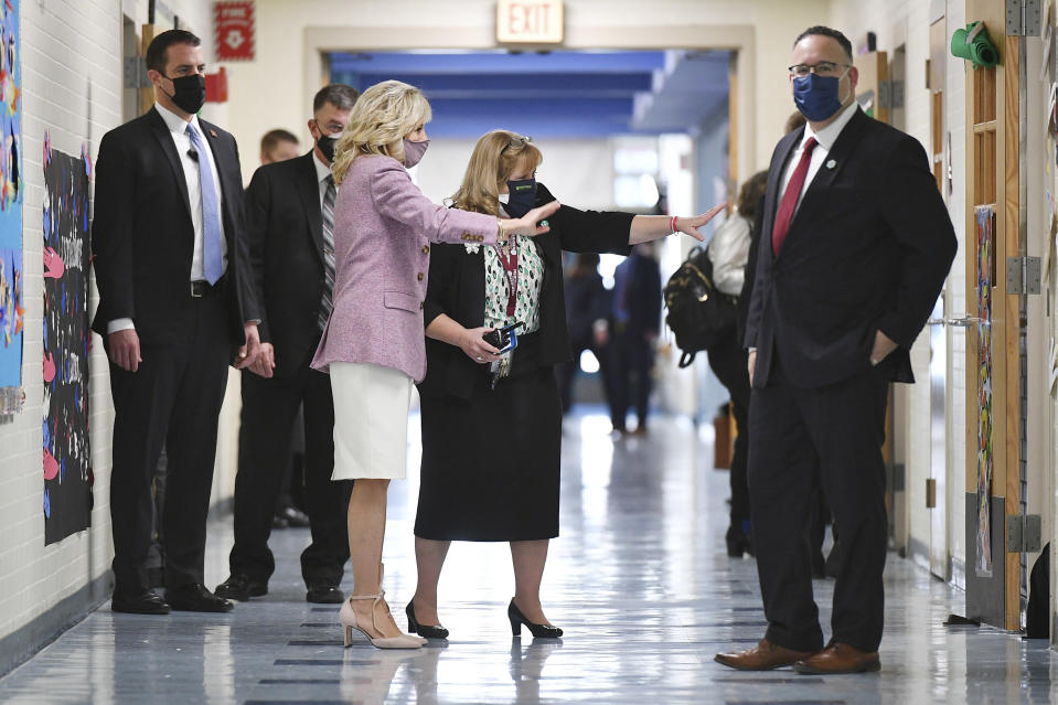 First lady Jill Biden waves to students in a classroom as she tours Benjamin Franklin Elementary School with Education Secretary Miguel Cardona, right, Wednesday, March 3, 2021 in Meriden, Ct. (Mandel Ngan/Pool via AP)