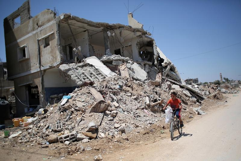 A Palestinian boy rides his bicycle past buildings that were destroyed during the 50-day war between Israel and Hamas militants in the summer of 2014, in the village of Khuzaa, in the southern Gaza Strip, June 15, 2015 (AFP Photo/Said Khatib)