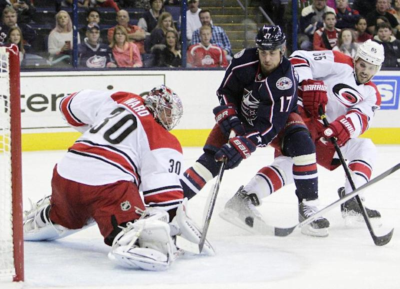 Carolina Hurricanes' Cam Ward, left, makes a save as teammate Ron Hainsey, right, and Columbus Blue Jackets' Brandon Dubinsky (17) look for the rebound during the second period of an NHL hockey game on Thursday, Sept. 26, 2013, in Columbus, Ohio. (AP Photo/Jay LaPrete)