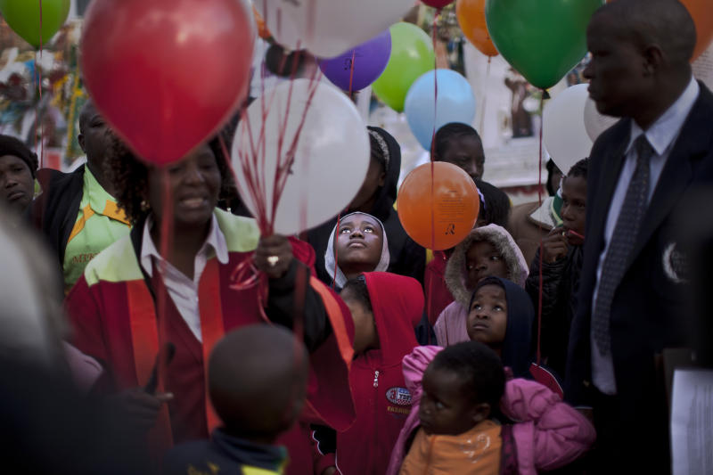 """Children, a choir and other well-wishers hold balloons to release them to mark former South African President Nelson Mandela completing his 27th day in hospital Thursday, correlating with the 27 years he spent in prison during the apartheid era, outside the Mediclinic Heart Hospital where he is being treated in Pretoria, South Africa, Friday, July 5, 2013. The former president's health is """"perilous,"""" according to documents filed in the court case that resulted in the remains of his three deceased children being reburied Thursday in their original graves. (AP Photo/Muhammed Muheisen)"""