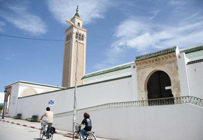 People ride their bicycle past a closed mosque in La Marsa district, just outside Tunis, Monday, May, 10, 2021. Tunisia announced on Friday strict new measures to try to contain the spread of the coronavirus, with the prime minister saying that the health system risks collapsing if something is not done. Houses of prayer are being ordered closed starting Sunday for a week, along with outdoor markets and large stores and malls. Shops selling food can remain open. (AP Photo/Hassene Dridi)