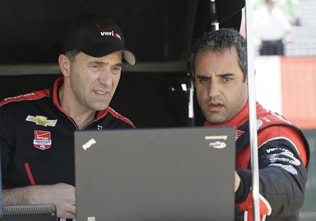 Driver Juan Pablo Montoya, right, talks with crew chief Greg Erwin after a practice session for the IndyCar Detroit Grand Prix auto race on Belle Isle in Detroit, Friday, May 30, 2014. (AP Photo/Carlos Osorio)