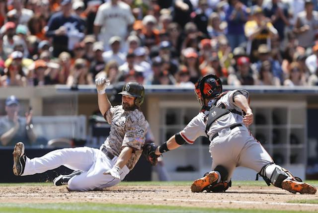 San Francisco Giants catcher Buster Posey, right, makes a swipe tag to San Diego Padres' Xavier Nady who is out trying to score from first on a bases-loaded double hit by Chase Headley in the third inning of a baseball game on Sunday, April 20, 2014, in San Diego. Nady was originally called safe but Giants manager Bruce Bochy appealed the call and it was overturned. (AP Photo/Lenny Ignelzi)