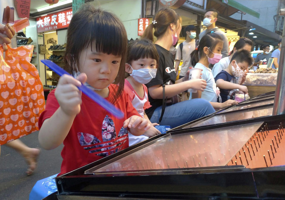 Children wear face masks to help curb the spread of the coronavirus as they play carnival games at a night market in Taipei, Taiwan, Sunday, May 3, 2020. (AP Photo/Chiang Ying-ying)