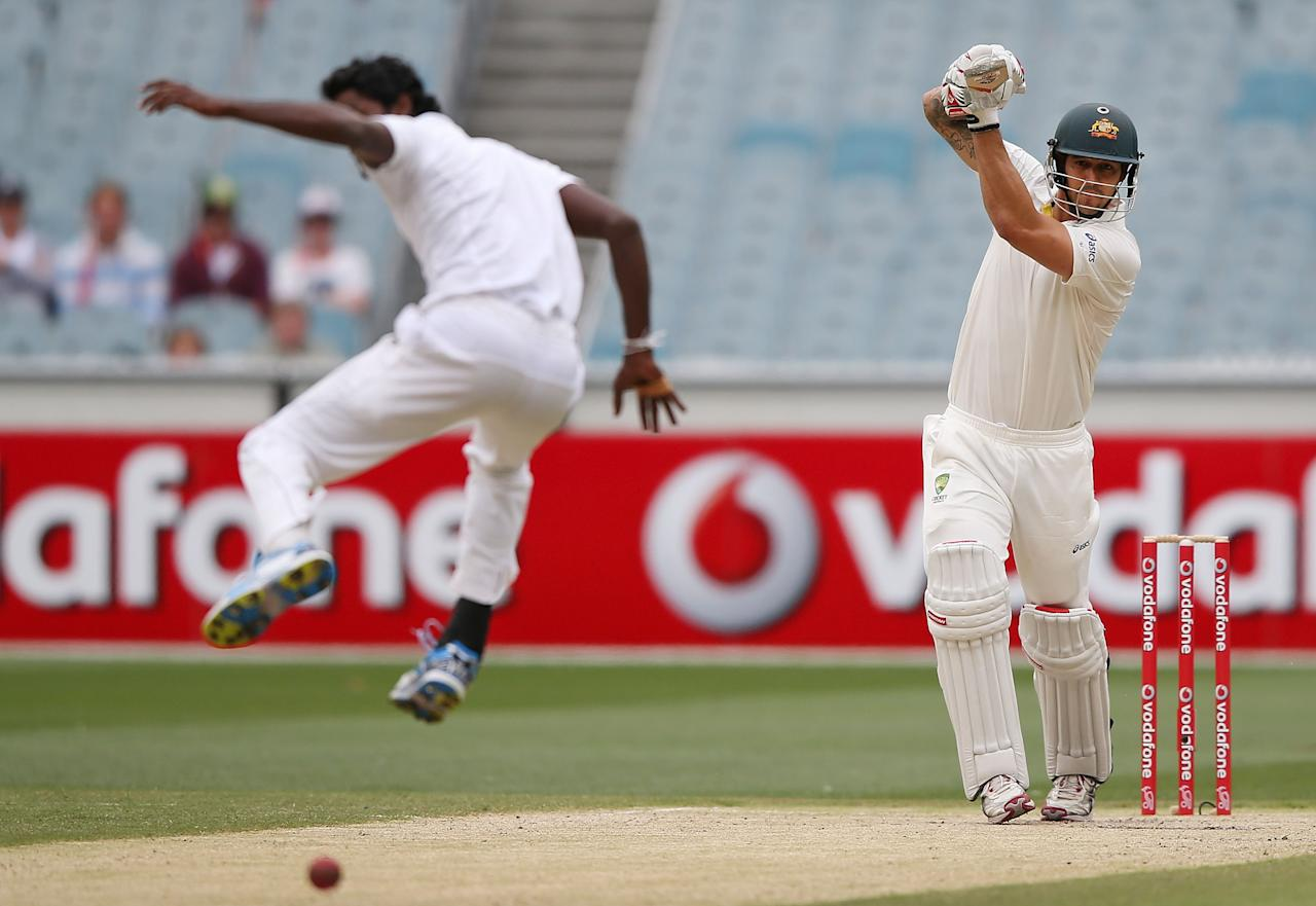MELBOURNE, AUSTRALIA - DECEMBER 28:  Mitchell Johnson of Australia hits the ball past Shaminda Eranga of Sri Lanka during day three of the Second Test match between Australia and Sri Lanka at Melbourne Cricket Ground on December 28, 2012 in Melbourne, Australia.  (Photo by Michael Dodge/Getty Images)