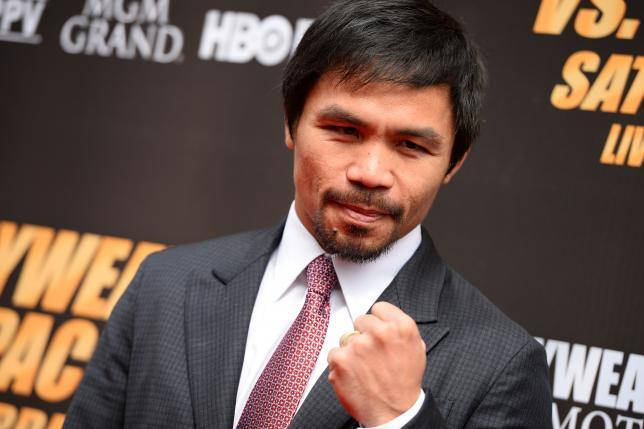 Boxer Manny Pacquiao poses on the red carpet before a joint press conference with Floyd Mayweather.