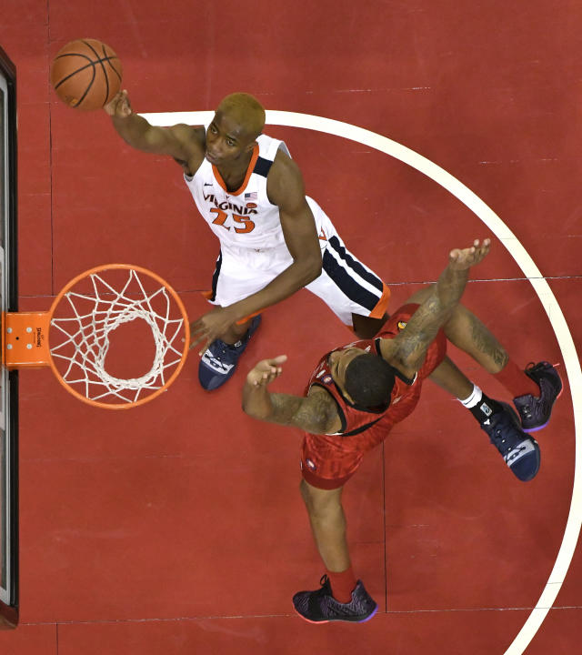 Virginia forward Mamadi Diakite (25) attempts a layup over the defense of Louisville center Malik Williams (5) during the first half of an NCAA college basketball game in Louisville, Ky., Saturday, Feb. 23, 2019. Virginia won 64-52. (AP Photo/Timothy D. Easley)