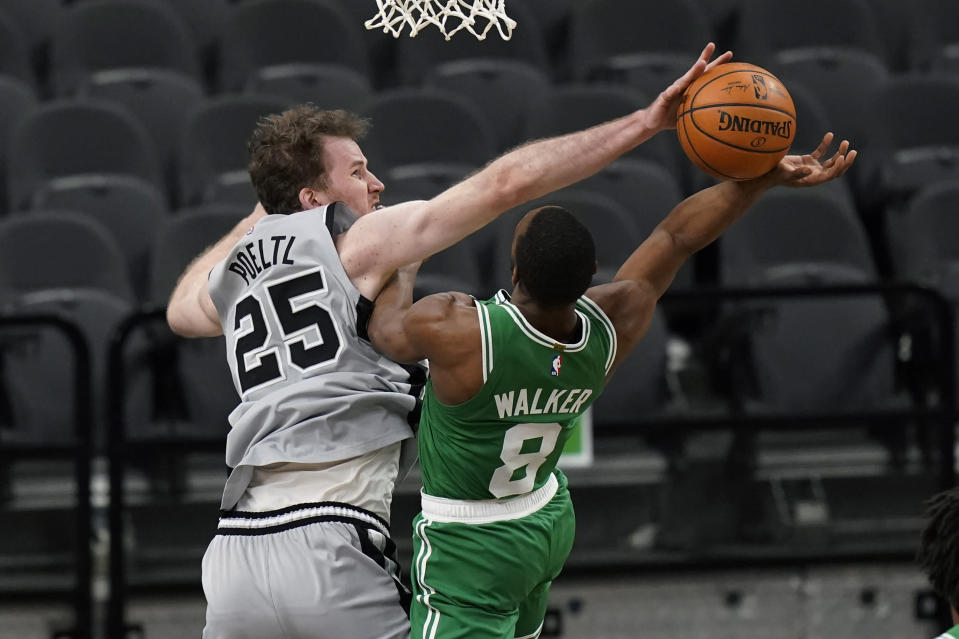 Boston Celtics guard Kemba Walker (8) is blocked by San Antonio Spurs center Jakob Poeltl (25) as he tries to score during the second half of an NBA basketball game in San Antonio, Wednesday, Jan. 27, 2021. (AP Photo/Eric Gay)