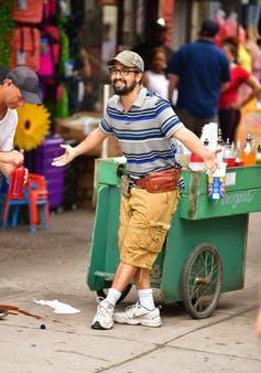 Lin-Manuel Miranda poses in front of a cart that sells flavored ice.