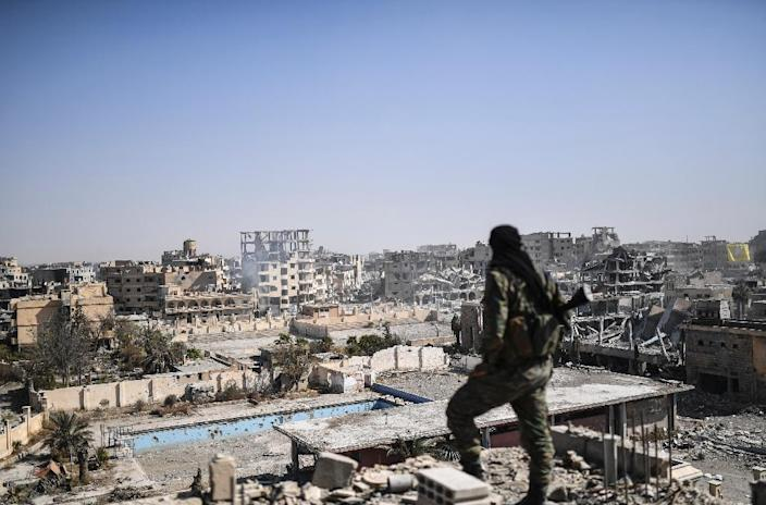 A Syrian fighter stands guard on a rooftop in Raqa on October 20, 2017 after the city's recapture from the Islamic State group (AFP Photo/BULENT KILIC)