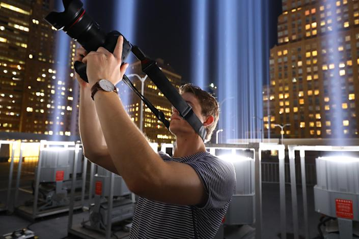 <p>A member of media takes a photo while attending a special viewing of the Tribute in Light on Sept. 5, 2018. (Photo: Gordon Donovan/Yahoo News) </p>