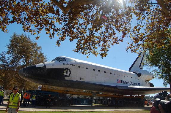 """Space shuttle Endeavour rolls toward its new display pavilion at the California Science Center in Los Angeles in the final stretch of its three-day, 12-mile (19 km) """"Mission 26"""" journey."""