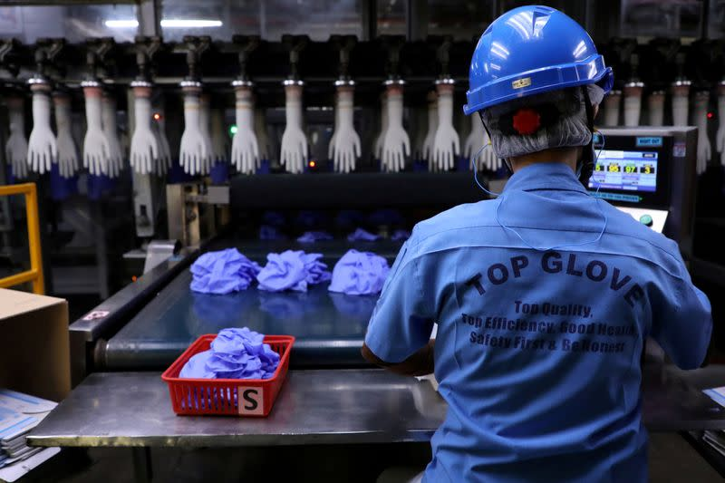 FILE PHOTO: A worker works at a production line in Top Glove factory in Shah Alam