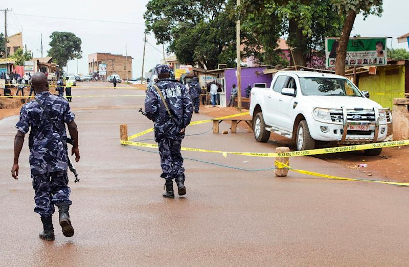 Police stand guard on March 31, 2015 at the scene in a suburb in Kampala where Uganda's acting assistant director of public prosecution Joan Kagezi was shot dead the previous day