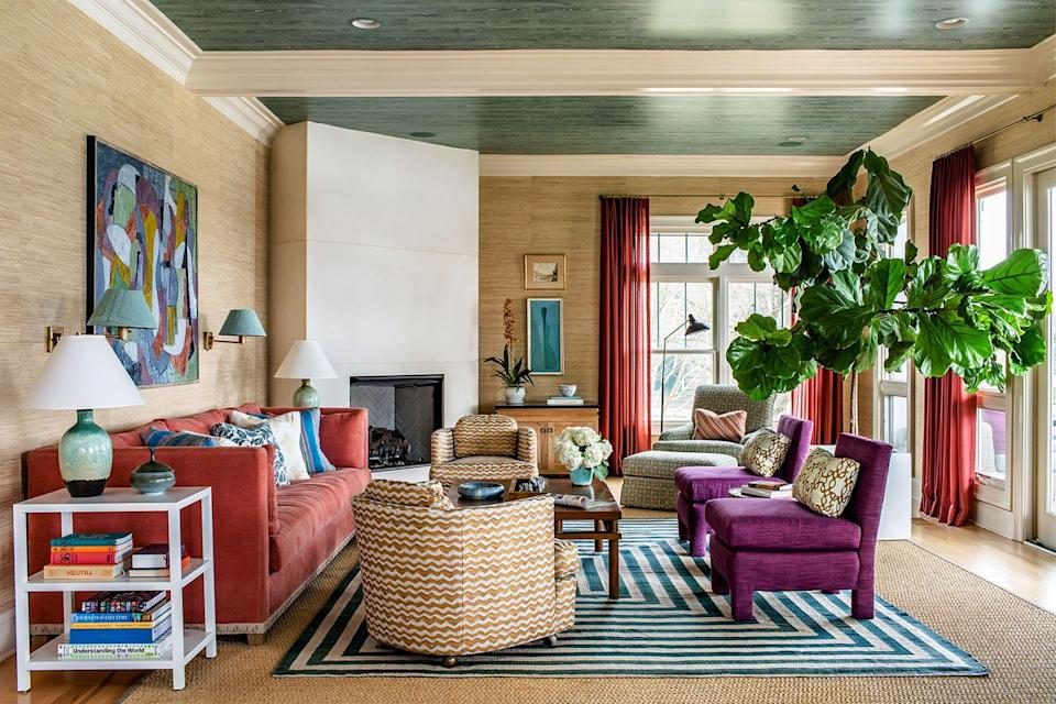 """<p>""""I grew up in a house with grasscloth and in my mind it's timeless,"""" says Charleston-based designer Angie Hranowsky. """"It's a wonderful way to add texture to a room and cozy up a space. They make beautiful patterned grasscloth now as well, in case you want something bolder or really want to make a statement.""""</p><p>Hranowsky says one of her favorite ways she's used grasscloth over the years is in this spacious, open living room. She covered the walls in a natural grasscloth—and the ceiling in a green faux wood wallpaper—to make the room feel more inviting and intimate.<br></p>"""