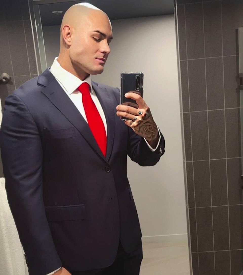 MAFS' Sam Ball wearing a blue suit and a red tie. His head is shaved