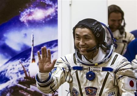 Wakata waves after donning a space suit shortly before the blast off for the ISS, at the Baikonur cosmodrome