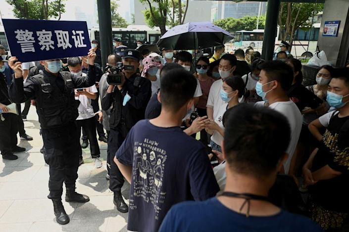 """Police officers survey people gathering at the Evergrande headquarters in Shenzhen, China on Sept. 16, 2021, as the Chinese property giant said it was facing """"unprecedented difficulties"""" but denied rumors that it was about to go under.<span class=""""copyright"""">NOEL CELIS/AFP via Getty Images</span>"""