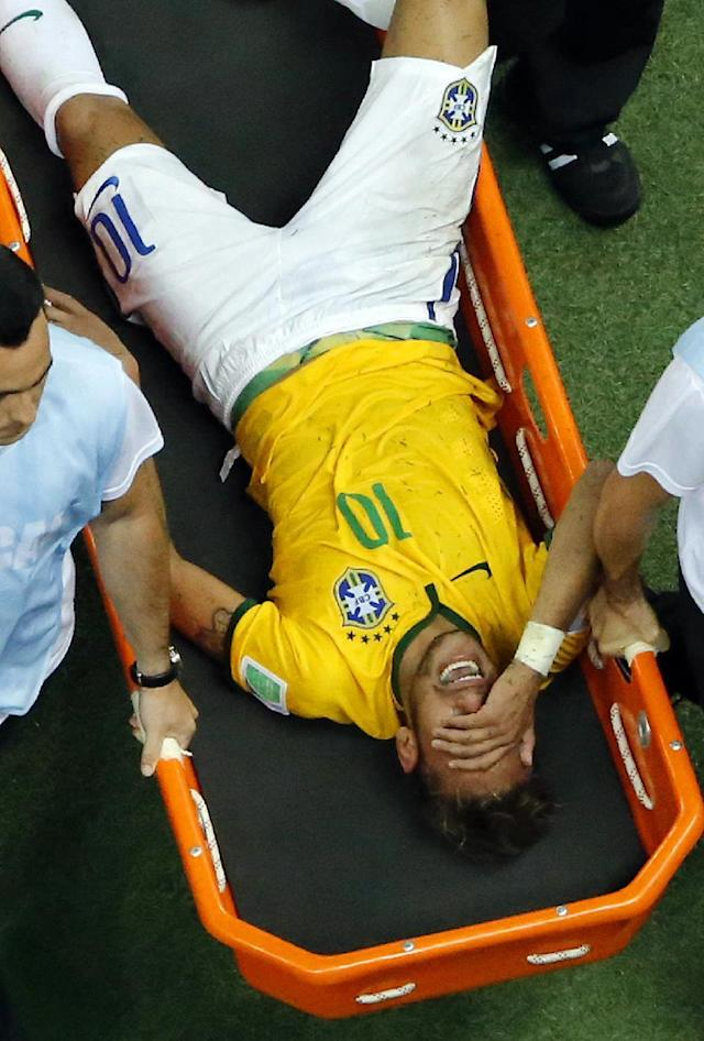 Brazil's Neymar is carried away after getting injured during the World Cup quarterfinal soccer match between Brazil and Colombia at the Arena Castelao in Fortaleza, Brazil, Friday, July 4, 2014. Brazil's team doctor says Neymar will miss the rest of the World Cup after breaking a vertebrae during the team's quarterfinal win over Colombia. (AP Photo/Fabrizio Bensch, pool)