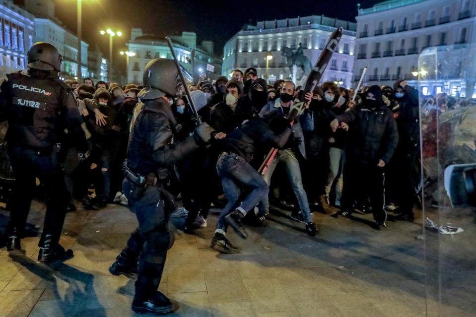 Police officers clash with demonstrators following a protest condemning the arrest of rap singer Pablo Hasel in Madrid, Spain, Wednesday, Feb. 17, 2021. Police fired rubber bullets and baton-charged protesters as clashes erupted for a second night in a row Wednesday at demonstrations over the arrest of Spanish rap artist Pablo Hasel. Many protesters threw objects at police and used rubbish containers and overturned motorbikes to block streets in both Madrid and Barcelona. (AP Photo/Manu Fernandez)