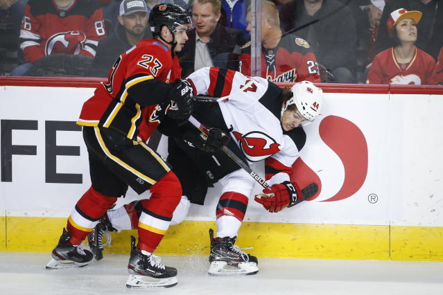 New Jersey Devils' Miles Wood, right, is checked by Calgary Flames' Sean Monahan during the second period of an NHL hockey game Thursday, Nov. 7, 2019, in Calgary, Alberta. (Jeff McIntosh/The Canadian Press via AP)