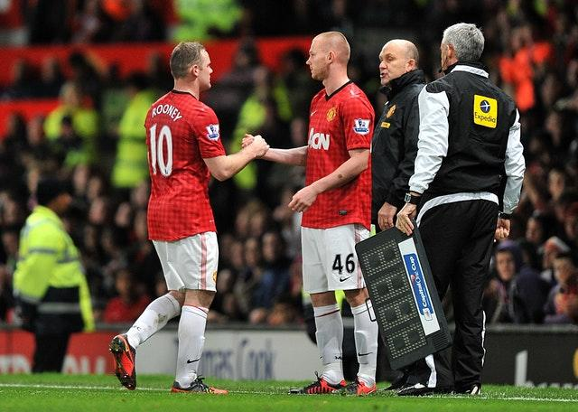 Ryan Tunnicliffe shakes hands with Wayne Rooney before coming on for his Manchester United debut in 2011