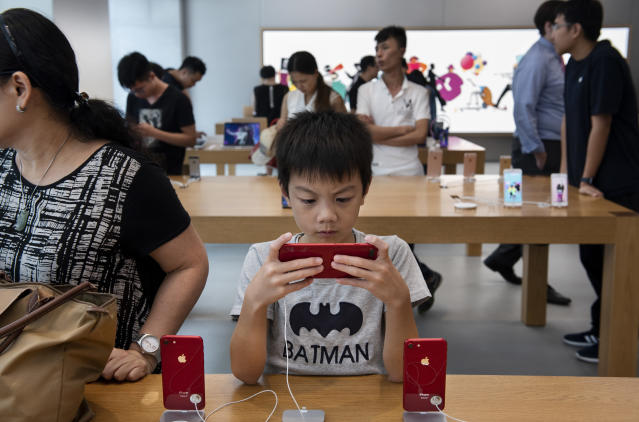 A boy plays a game on an IPhone at the Apple Store in Causeway Bay, Hong Kong. (Photo: Miguel Candela/SOPA Images/LightRocket via Getty Images)