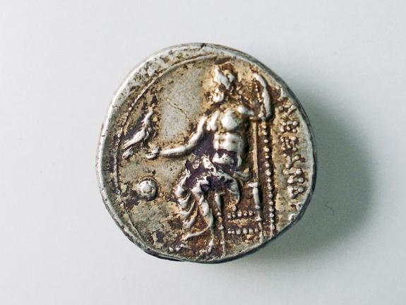The reverse side of the coin has an image of Zeus and an inscription of Alexander the Great's name.