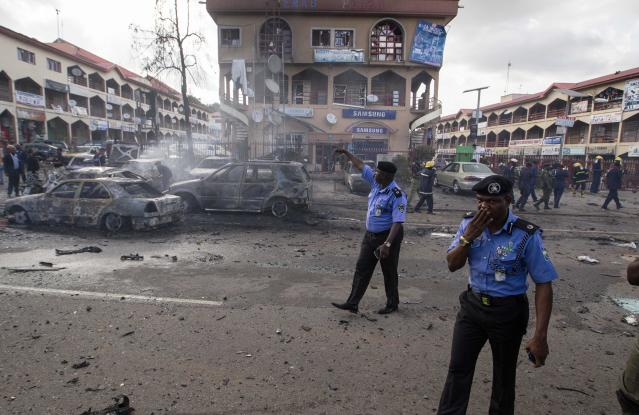 Policemen walk towards burnt vehicles at the scene of a blast at a business district in Abuja June 25, 2014. At least 21 people were killed when a suspected bomb tore through the crowded shopping district in the Nigerian capital Abuja during rush hour on Wednesday, police said, adding to the toll of thousands killed in attacks this year. REUTERS/Afolabi Sotunde (NIGERIA - Tags: CIVIL UNREST MILITARY TPX IMAGES OF THE DAY)