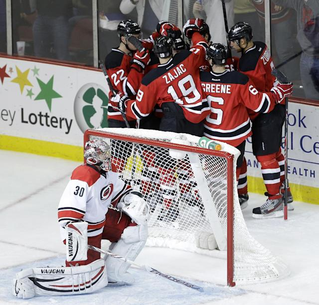 Carolina Hurricanes goalie Cam Ward, bottom, kneels at his goal while members of the New Jersey Devils celebrate a goal by Jaromir Jagr, of the Czech Republic, during the third period of an NHL hockey game, Wednesday, Nov. 27, 2013, in Newark, N.J. The Hurricanes won 4-3. (AP Photo/Julio Cortez)