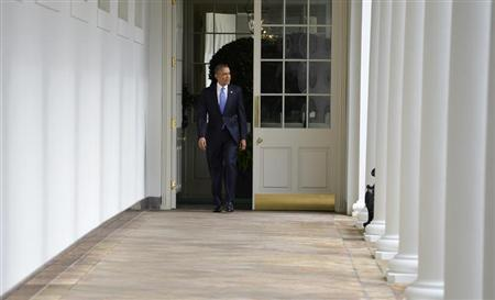 U.S. President Obama walks the colonnade from the residence of the White House to the Oval Office as he continues preparation of his State of the Union address, in Washington