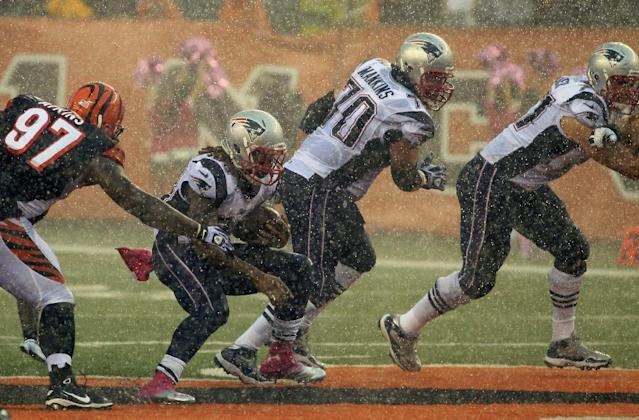 New England Patriots running back Brandon Bolden runs past Cincinnati Bengals defensive tackle Geno Atkins (97) in a pouring rain late in the fourth quarter of an NFL football game, Sunday, Oct. 6, 2013, in Cincinnati. Guard Logan Mankins (70) and tackle Nate Solder block at right. Cincinnati won 13-6. (AP Photo/Tom Uhlman)