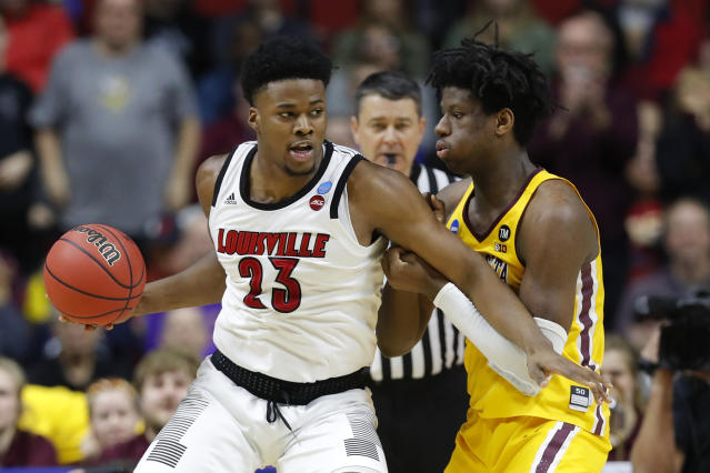 Louisville center Steven Enoch (23) drives around Minnesota center Daniel Oturu, right, during a first round men's college basketball game in the NCAA Tournament, Thursday, March 21, 2019, in Des Moines, Iowa. (AP Photo/Charlie Neibergall)
