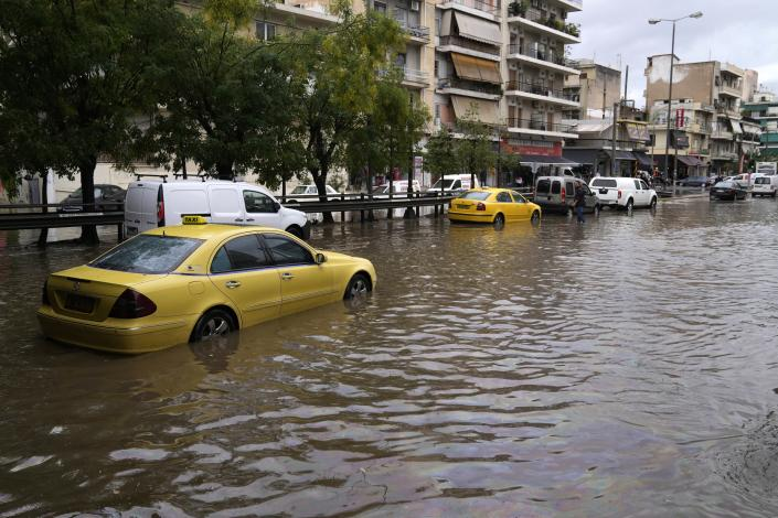A taxi is stranded as other vehicles cross a flooded avenue in Athens, Thursday, Oct. 14, 2021. Storms battered the Greek capital and other parts of southern Greece, causing traffic disruption and some road closures. (AP Photo/Thanassis Stavrakis)
