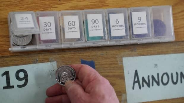 An Alcoholics Anonymous member holds a coin that indicates 24 hours of sobriety.