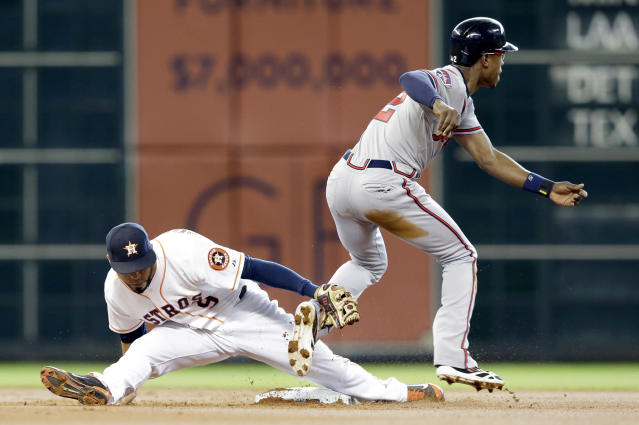 Houston Astros' Marwin Gonzalez, left, vainly tries to tag Atlanta Braves' B.J. Upton (2) who steals second base and then goes on to third on a throwing error by Astros catcher Jason Castro in the first inning of a baseball game Thursday, June 26, 2014, in Houston. (AP Photo/Pat Sullivan)