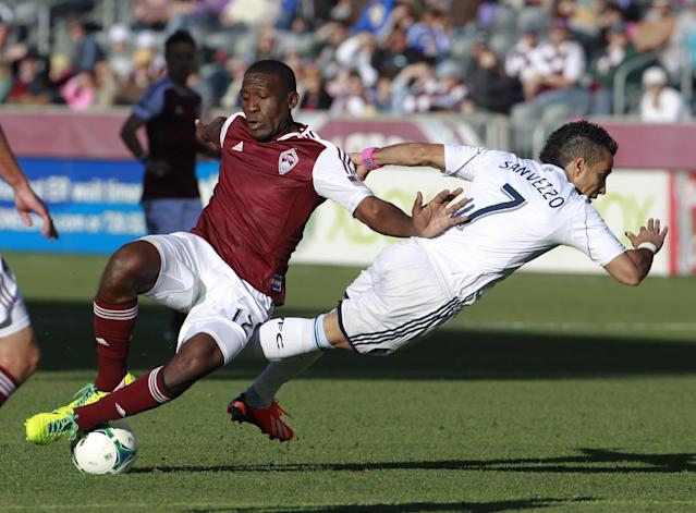 Vancouver Whitecaps forward Camilo Sanvezzo, right, is sent flying after getting tied up with Colorado Rapids midfielder Hendry Thomas in the first half of a MLS soccer game in Commerce City, Colo., on Saturday, Oct. 19, 2013. (AP Photo/David Zalubowski)