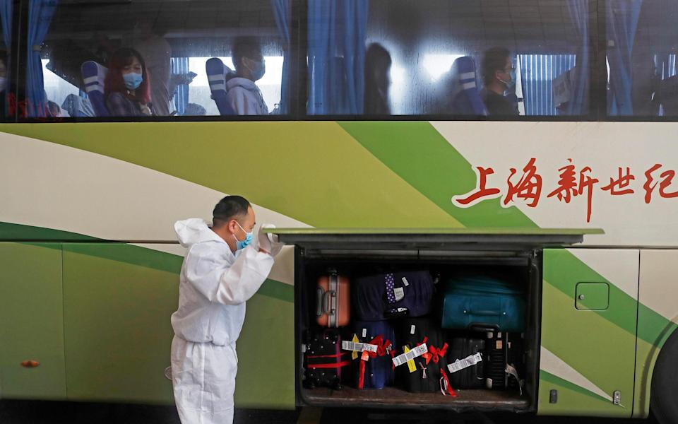In Shanghai, arrivals from the US wait in a bus for their transfer to a quarantine hotel – where they must stay for 14 days - Getty