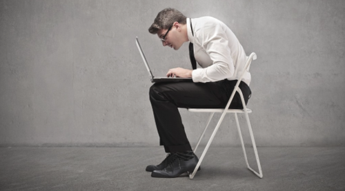 Man hunched over laptop