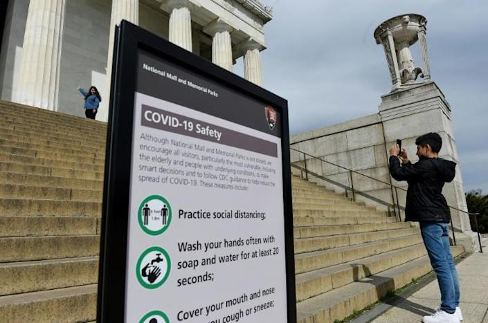 Tourists take pictures near a sign informing about coronavirus safety measures at the Lincoln Memorial on March 27, 2020 in Washington, DC (AFP Photo/Olivier DOULIERY)