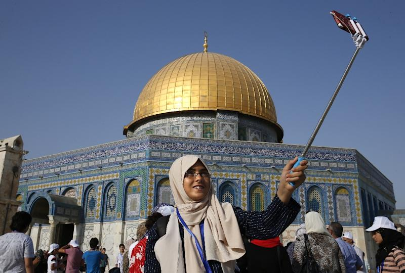 A Palestinian girl from Gaza takes a selfie outside the Dome of the Rock mosque in the Al-Aqsa mosque compound in Jerusalem's Old City on August 20, 2017 (AFP Photo/AHMAD GHARABLI)