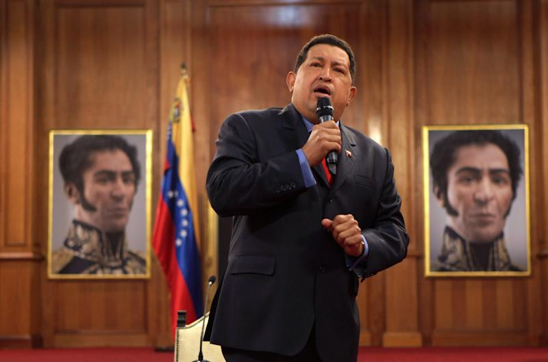 FILE - In an Oct. 12, 2012 file photo Venezuela's President Hugo Chavez is flanked by portraits of Venezuelan independence hero Simon Bolivar, during a press conference at the Miraflores palace in Caracas, Venezuela. Chavez returned home to Venezuela early Monday Feb. 18, 2012, after more than two months of medical treatment in Cuba following cancer surgery. (AP Photo/Rodrigo Abd, file)