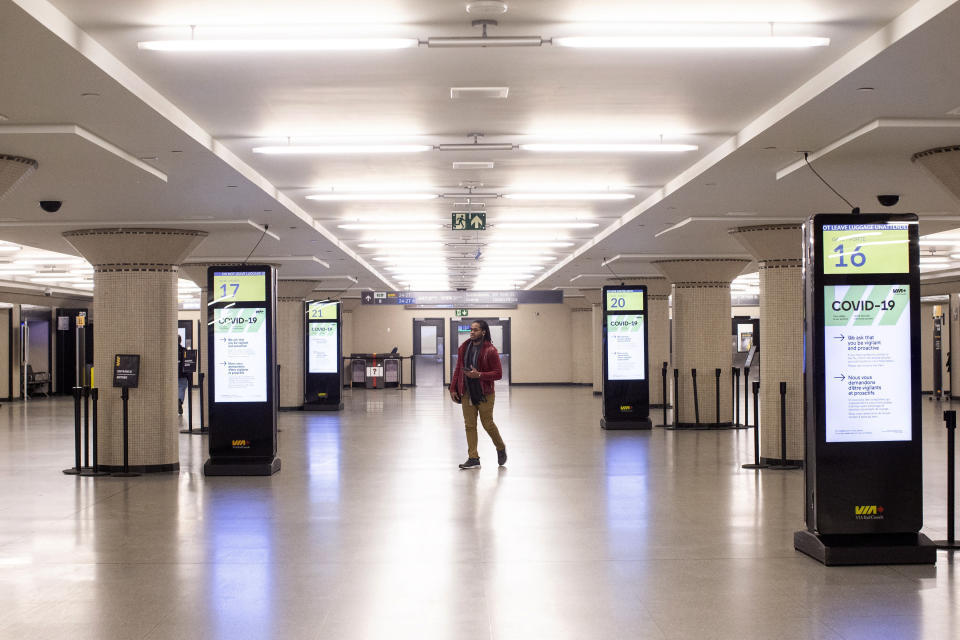 A man walks through a VIA Rail concourse area at Toronto's Union Station during the coronavirus outbreak, Saturday, March 28, 2020. Canadian Prime Minister Justin Trudeau announced that those showing symptoms of COVID-19 will be barred from domestic air and rail travel as of this coming Monday. (Chris Young/The Canadian Press via AP)