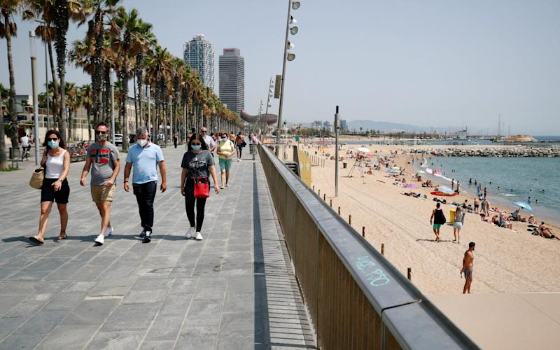 People wearing protective masks walk along the Barceloneta beach after Catalonia's regional authorities decided to make mandatory the use of face masks in public at all times, during the outbreak of the coronavirus disease (COVID-19), in Barcelona, Spain July 9, 2020. - Albert Gea/Reuters