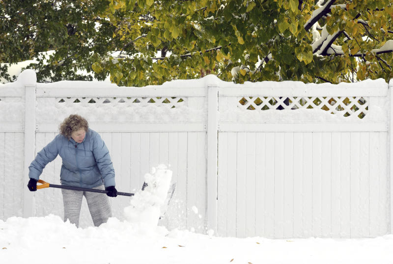 Anne Haugarth shovels the heavy, wet snow from a sidewalk in front of her home, Friday, Oct. 11, 2019 in Bismarck, N.D.  North Dakota Gov. Doug Burgum on Friday activated the state's emergency plan due to what he called a crippling snowstorm that closed major highways and had farmers and ranchers bracing for the potential of huge crop and livestock losses. (Mike McCleary/The Bismarck Tribune via AP)